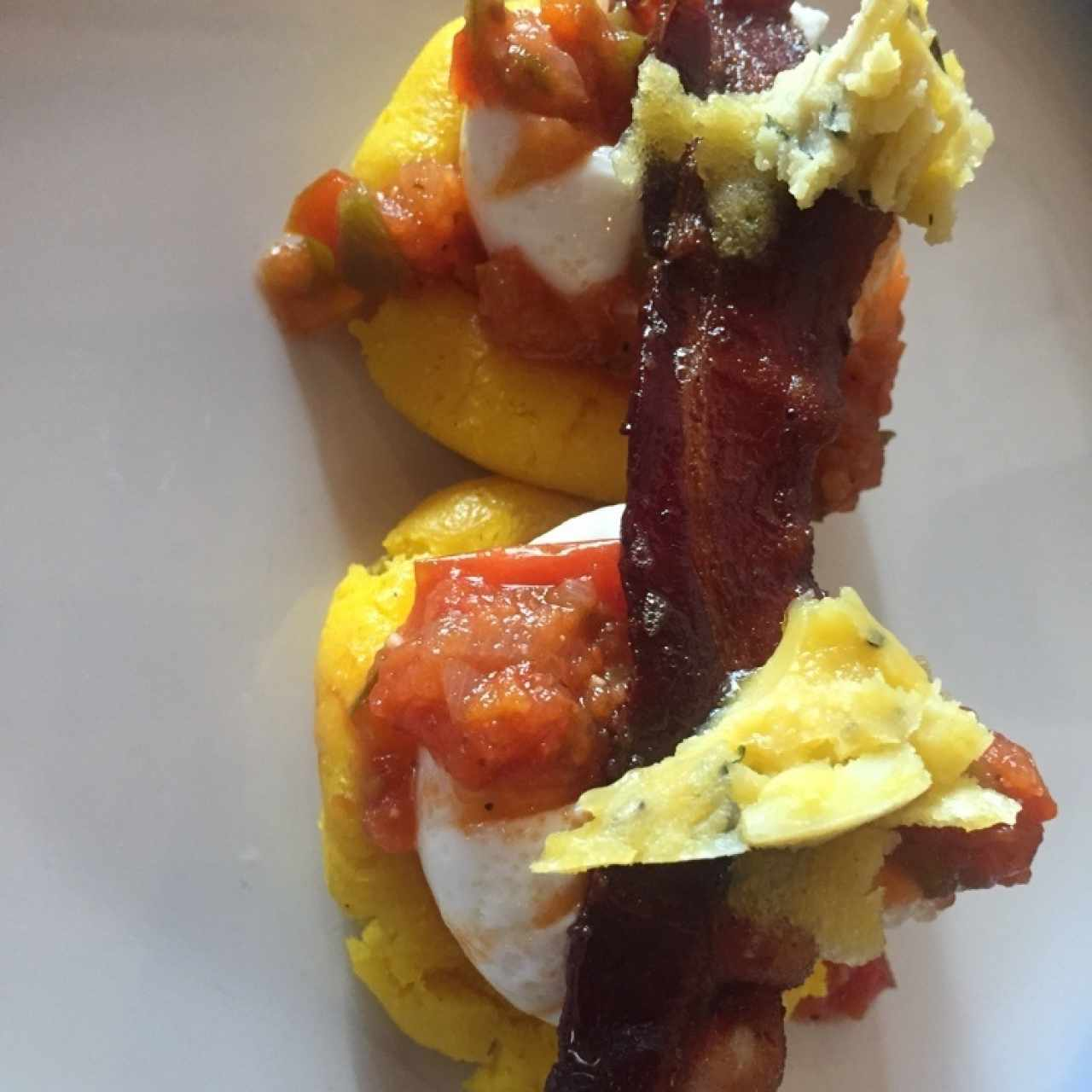 huevos escalfados sobre changa y bacon